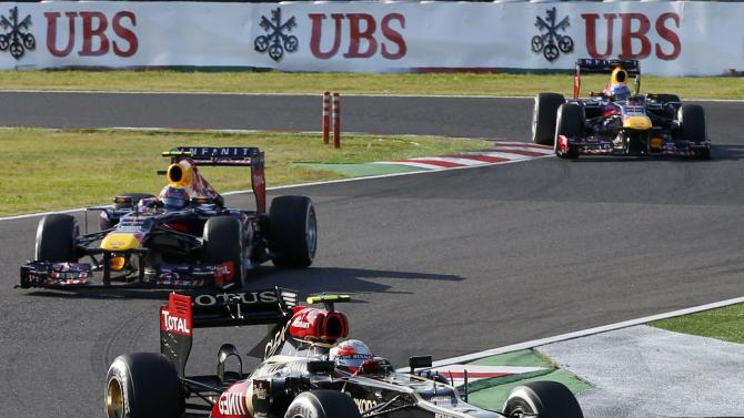 Lotus Formula One driver Grosjean of France drives ahead of Red Bull Formula One driver Webber of Australia during the Japanese F1 Grand Prix at the Suzuka circuit