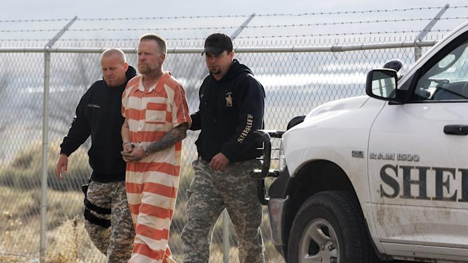 "Sanpete Sheriff's Officers escort Troy James Knapp, 45, to the Sanpete County Jail Tuesday, April 2, 2013, in Manti, Utah. Authorities on Tuesday captured Knapp, an elusive survivalist who is suspected of burglarizing Utah cabins and leaving some covered with threats and bullet holes — ending a saga that began six years ago and drew in police and residents around the state. Knapp, dubbed the ""Mountain Man"" by cabin owners, was taken into custody in the snowy mountains outside of Ferron in central Utah after firing several shots at officers in a helicopter, authorities said. (AP Photo/Rick Bowmer)"
