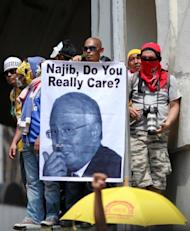 A protester is seen holding a picture of Malaysia's prime Minister Najib Razak during a mass rally organized by Bersih 3.0, calling for electoral reform, in Kuala Lumpur, in April 2012. Thousands of protesters gathered in the Malaysian capital to demand electoral reforms, defying a lockdown of central Kuala Lumpur