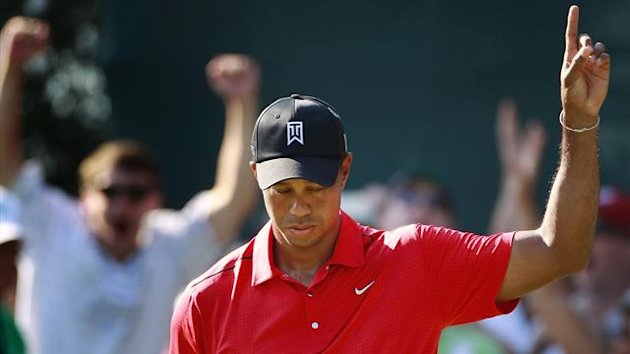Tiger Woods of the U.S. reacts to his birdie putt on the 15th hole during the final round of the AT&T National golf tournament at the Congressional Country Club in Bethesda, Maryland