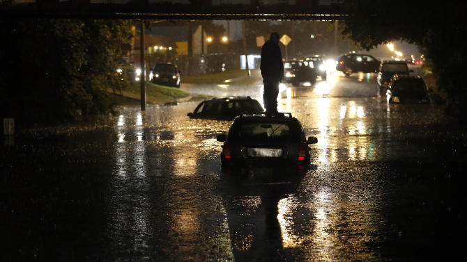 A man stands on top of his car as it is flooded on S. May Ave near SW 25th in Oklahoma City, Friday, May 31, 2013, following flooding after a severe thunderstorm moved through Oklahoma CIty. (AP Photo/The Oklahoman, Sarah Phipps) LOCAL STATIONS OUT (KFOR, KOCO, KWTV, KOKH, KAUT OUT); LOCAL WEBSITES OUT; LOCAL PRINT OUT (EDMOND SUN OUT, OKLAHOMA GAZETTE OUT) TABLOIDS OUT