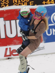 Sarah Schleper holds her son Lasse as she skies down the course during an alpine ski, women's World Cup slalom, in Lienz, Austria, Thursday, Dec. 29, 2011. American skier Sarah Schleper, who competed in four Winter Olympics, says Thursday's slalom will be the last World Cup race of her career. The 32-year-old Schleper will retire after 15 years and 186 races since making her World Cup debut in her native Vail, Colorado, in 1995. (AP Photo/Armando Trovati)