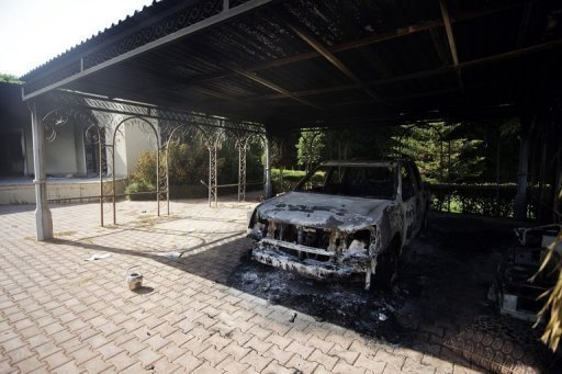 "A burnt vehicle inside the US consulate compound in Benghazi on September 13. The White House has for the first time described the assault on the US consulate in Benghazi, which killed four Americans, as a ""terrorist attack"" that could have links to Al-Qaeda."