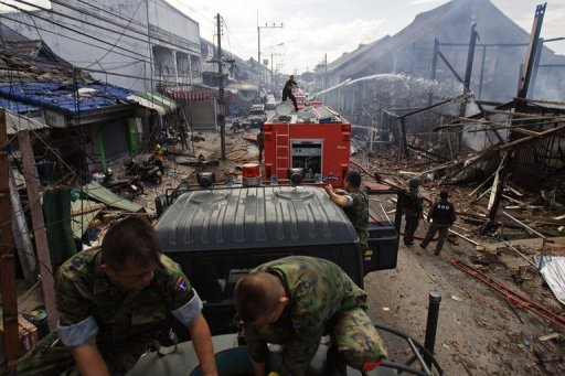 Thai members of the security forces gather at the site of a car bomb attack at a packed market in Sai Buri. At least six people were killed and more than 40 were wounded after a car bomb exploded in a busy shopping street in Thailand's insurgency-hit south, officials told AFP.