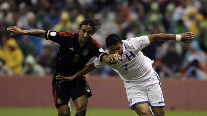 Emilio Izaguirre of Honduras battles for the ball with Fernando Arce of Mexico during their 2014 World Cup qualifying soccer match in Mexico City