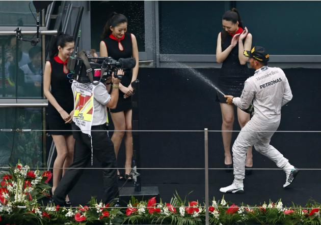 First-placed Mercedes Formula One driver Hamilton of Britain sprays champagne to grid girls as he celebrates his win after Chinese F1 Grand Prix at Shanghai International circuit
