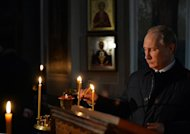 Russia's President Vladimir Putin lights a candle at a church, in Lermontovo village near Penza, on October 15, 2014