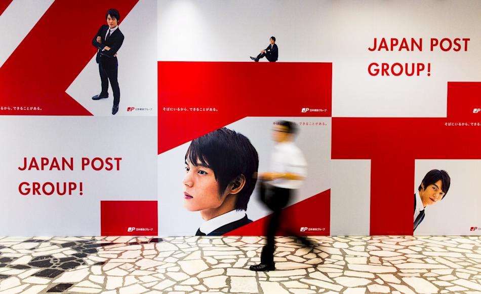 File photo of a man walking past an advertising poster in headquarters of Japan Post in Tokyo