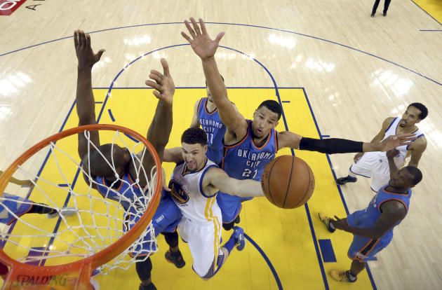 Golden State Warriors guard Klay Thompson, center, shoots between Oklahoma City Thunder forward Serge Ibaka, left, and guard Andre Roberson (21) during the first half of Game 7 of the NBA basketball W