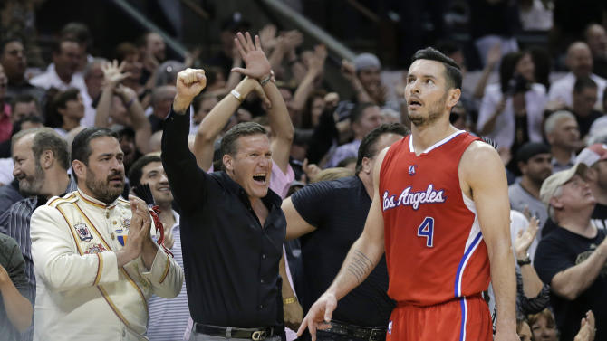 Los Angeles Clippers' J.J. Redick (4) walks past cheering San Antonio Spurs fans during the first half of Game 3 in an NBA basketball first-round playoff series, Friday, April 24, 2015, in San Antonio. (AP Photo/Darren Abate)