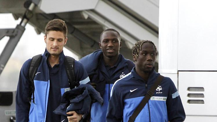 French national soccer team players Olivier Giroud, left, Bacary Sagna, right, and Moussa Sissoko arrive at the Kiev airport ahead of their 2014 World Cup qualifying play off first leg soccer match against Ukraine  in Kiev, Ukraine, Thursday, Nov. 14, 2013