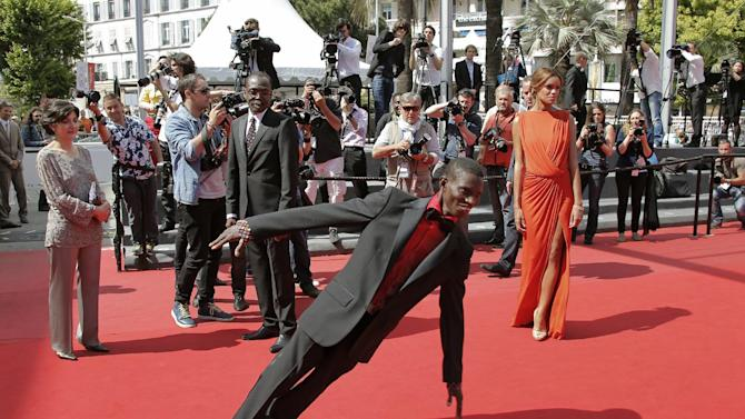 Actor Souleymane Deme, foreground, performs a dance as producer Florence Stern, left, director Mahamat-Saleh Haroun, rear centre, and actress Anais Monory, right, watch him as they arrive for the screening of Grigris at the 66th international film festival, in Cannes, southern France, Wednesday, May 22, 2013. (AP Photo/Lionel Cironneau)