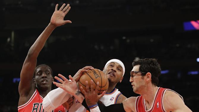 Chicago Bulls guard Kirk Hinrich (12) gets tangled up with New York Knicks forward Carmelo Anthony (7) as Chicago Bulls forward Tony Snell (20) defends in the first half of their NBA basketball game at Madison Square Garden in New York, Wednesday, Dec. 11, 2013