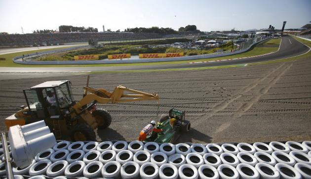 Track marshalls remove the car of Caterham Formula One driver van der Garde of Netherlands after he crashed, during the Japanese F1 Grand Prix at the Suzuka circuit