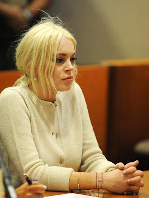 FILE - In this Wednesday, Dec. 14, 2011 file photo, Lindsay Lohan appears in court during progress report session at the Los Angeles Superior Court in Los Angeles. Lohan is facing a federal tax lien for nearly $94,000 the government says she owes for 2009 and was sued Tuesday, Jan. 11, 2012 in Los Angeles by a photographer who claims he was struck in January 2010 by a car the actress was riding in. (AP Photo/Michael Nelson, Pool)