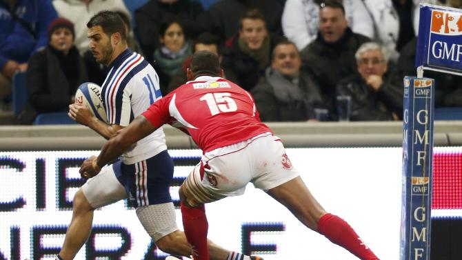 France's Sofiane Guitoune is challenged by Tonga's Vungakoto Lilo during their rugby test match in Le Havre