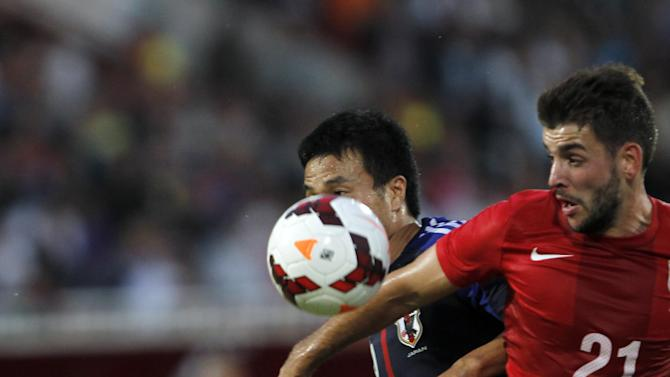Japan's Yasuyuki Konno, center, challenges for the ball with Serbia's Filip Djordjevic during Serbian Dejan Stankovic's farewell match, at Karadjordje stadium in Novi Sad, Serbia, Friday, Oct. 11, 2013. Stankovic,  who is retired ,  played for Red Star Belgrade (1994-1998), Lazio (1998-2004) and Inter Milan (2004-2013). After this match Stankovic will have the largest number of appearances in Serbian national team history