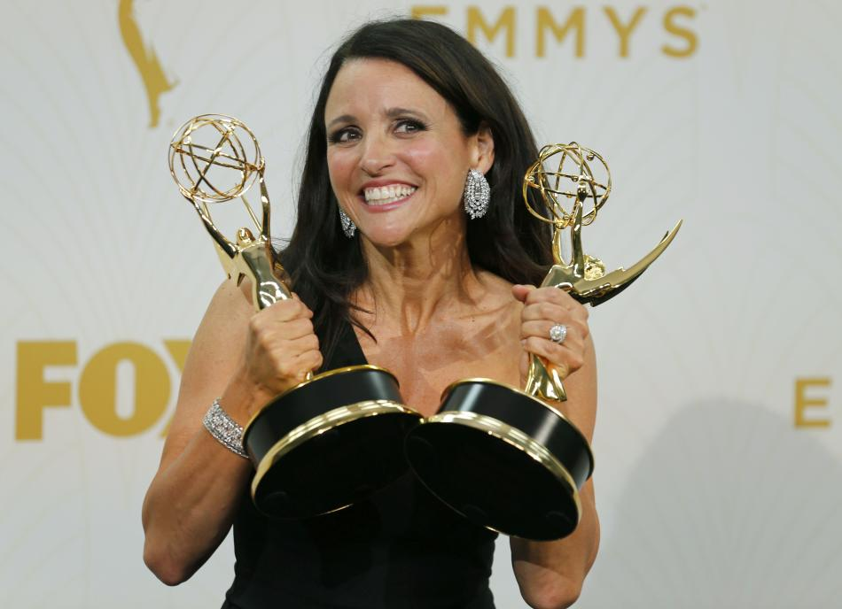Actress Julia Louis-Dreyfus poses backstage as she holds the awards for Outstanding Comedy Series and for Outstanding Lead Actress In A Comedy Series for her role in HBO's