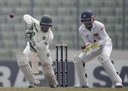 Bangladesh's Mominul Haque plays a ball as Sri Lanka's wicketkeeper Dinesh Chandimal watches during their fourth day of their first test cricket match of the series in Dhaka.
