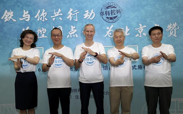 WHO representative demonstrates with other participants an anti-smoking gesture, which asked people to stop smoking, during an event to raise awareness of the new smoking regulations, at a subway stat