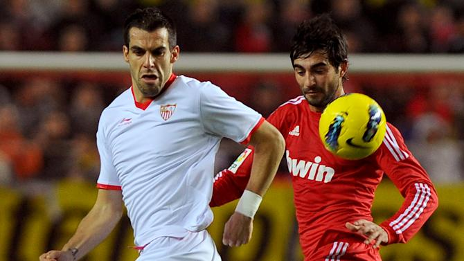 Sevilla's forward Alvaro Negredo (L) vies for the ball with Real Madrid's defender Raul Albiol (R) during the Spanish league football match Sevilla FC vs Real Madrid on December 17, 2011 at Ramon Sanchez Pizjuan stadium in Sevilla.    AFP PHOTO/ JORGE GUERRERO (Photo credit should read Jorge Guerrero/AFP/Getty Images)