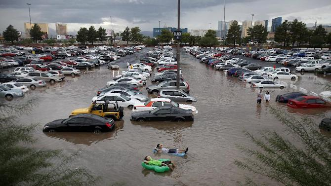 University of Nevada, Las Vegas students Ryan Klorman, top, and Markus Adams, relax on inflatable pool toys in floodwater at UNLV in Las Vegas Tuesday, Sept. 11, 2012. Intense thunderstorms drenched parts of the Southwest on Tuesday, delaying flights and stranding motorists in the Las Vegas area and flooding two mobile home parks in Southern California. (AP Photo/Las Vegas Review-Journal, John Locher)