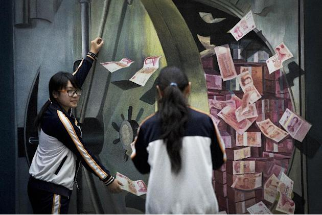 A woman takes a souvenir photo for her friend posing with a 3-D painting of a vault loaded with piles of 100 Chinese yuan (US$16.17) notes at a shopping mall in Beijing, China Friday, May 22, 2015. Ne