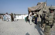 US army SPC Arianna Harvey (right) and Sergeant Lolita Ray (2nd right) stand guard as Afghan security personnel checks workers entering Camp Clark in Mandozai district, Khost province, last July. A suicide attack on a police checkpost in southeastern Afghanistan has killed at least nine people, three of them policemen, an official says
