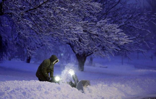 A local resident clears snow from his driveway after an overnight snowfall left many schools and businesses closed for the day, Thursday, Dec. 20, 2012, in Urbandale, Iowa. (AP Photo/Charlie Neibergal