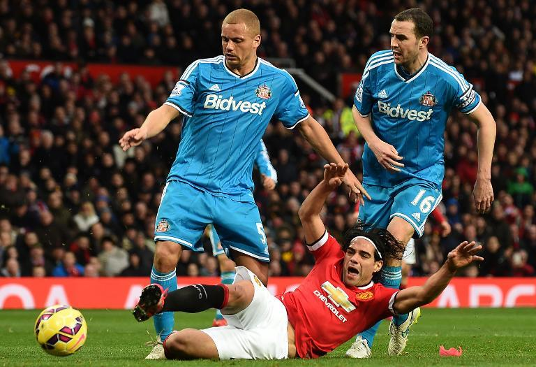 Manchester United's Radamel Falcao falls after clashing with Sunderland's Wes Brown (L) and John O'Shea, leading to a penalty and a red card for Brown, during their English Premier League