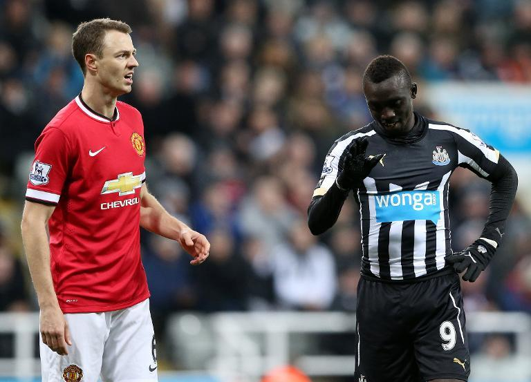 Manchester United's Northern Irish defender Jonny Evans (L) reacting next to Newcastle United's Senegalese striker Papiss Cisse on March 4, 2015