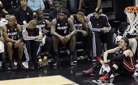 Miami Heat's LeBron James sits with his teammates near the end of their loss to the San Antonio Spurs in Game 5 of their NBA Finals basketball series in San Antonio