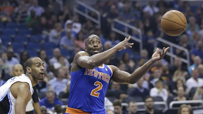 New York Knicks' Raymond Felton (2) passes the ball as he is guarded by Orlando Magic's Arron Afflalo, left, in the first half of an NBA basketball game in Orlando, Fla., Monday, Dec. 23, 2013