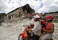 A family riding a motorcycle looks at a damaged church after an earthquake in the tourist town of Lobok, Bohol October 17, 2013. The Philippines started to clear roads blocked by debris on Thursday as it reckoned up the cost of this week's powerful earthquake, with the death toll rising to at least 158. Tens of thousands of residents of Bohol island, which took the brunt of Tuesday's 7.2 magnitude quake, remained living outdoors, for fear of aftershocks bringing down damaged homes. REUTERS/Erik De Castro (PHILIPPINES - Tags: DISASTER RELIGION)