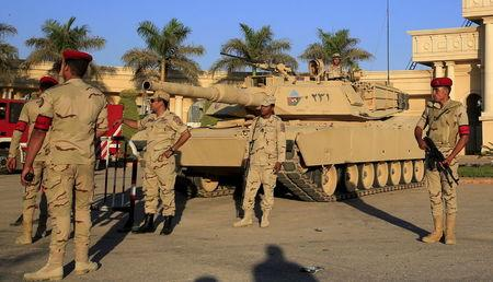 """Egyptian army soldiers with a tank stand guard in front of the main gate at the Borg El Arab """"Army Stadium"""" before the Egyptian Premier League derby soccer match between Al-Ahly and El Zamal"""
