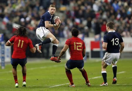 Scotland's Russell jumps to catch a pass in front of France's Thomas and Fofana during their Six Nations rugby union match in Saint-Denis