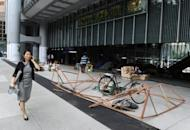 A pedestrian walks past a display by the anti-capitalist 'Occupy' movement in Hong Kong, on the ground level of the HSBC building in Hong Kong, on June 25. HSBC on Monday sought legal permission to evict the protesters, one of the last remnants of the 'Occupy' movement in Asia