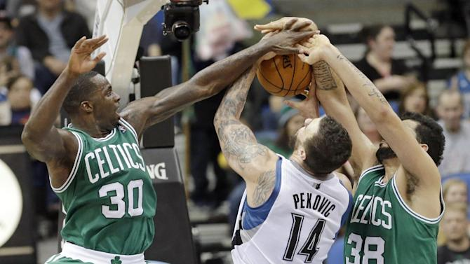 Minnesota Timberwolves' Nikola Pekovic (14), of Montenegro, tries to keep control of the ball as Boston Celtics' Brandon Bass, left, and Vitor Faverani, of Brazil, defend in the second half of an NBA basketball game on Saturday, Nov. 16, 2013, Minneapolis. The Timberwolves won 106-88