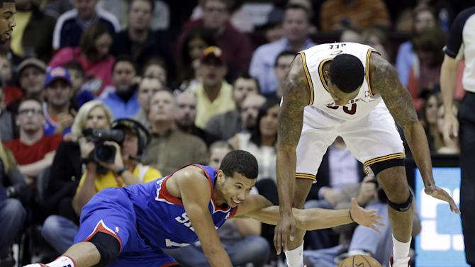 Philadelphia 76ers' Michael Carter-Williams, left, and Cleveland Cavaliers' Alonzo Gee reach for a loose ball during the first quarter of an NBA basketball game Saturday, Nov. 9, 2013, in Cleveland