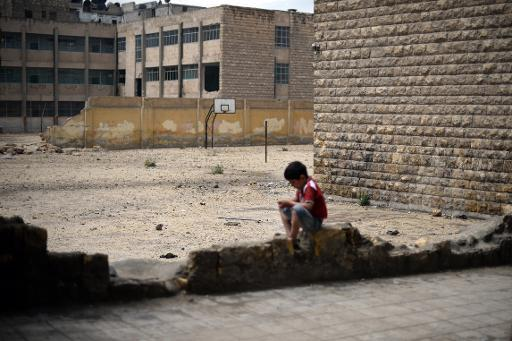 A boy sits next to a heavily damaged school in the northern Syrian city of Aleppo on April 17, 2013
