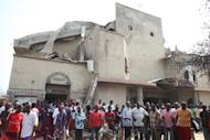 People stand in front of the partially destroyed St Theresa Catholic Church after a bomb blast in the Madala Zuba district of Nigeria's capital Abuja on December 25, 2011. Gunmen attacked a church in volatile northern Nigeria during a Christmas Eve service, killing six people including the pastor, before setting the building ablaze, residents and police said Tuesday