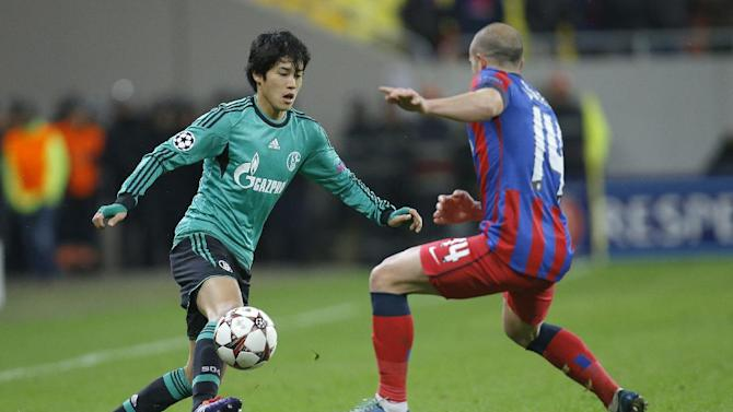 Schalke's Atsuto Uchida, left, controls the ball with Bucharest's Iasmin Latovlevici, during their Champions League Group E soccer match, at the National Arena in Bucharest, Romania, Tuesday, Nov. 26, 2013