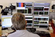 A trader looks at screens showing stock exchange share index in Paris, 2011. European stock markets rose and the euro gained against the dollar as investors looked ahead to a key IMF meeting and weekend French elections, and also kept watch over Spain