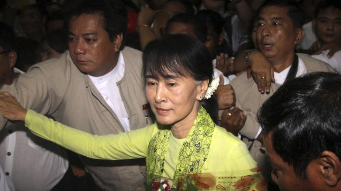 In this Sunday, Sept. 16, 2012 photo, Myanmar opposition Leader Aung San Suu Kyi, center, arrives at Yangon International airport, Myanmar, to depart for the U.S. in Yangon. Suu Kyi left Sunday on her first U.S. trip since she was put under house arrest in1990. She will be feted in Washington this week and presented Congress's highest award, the latest milestone in her journey from political prisoner to globe-trotting stateswoman. The Nobel Peace laureate's 17-day U.S. tour, starting Monday, comes as the Obama administration considers easing its remaining sanctions on the country also known as Burma. (AP Photo/Khin Maung Win)