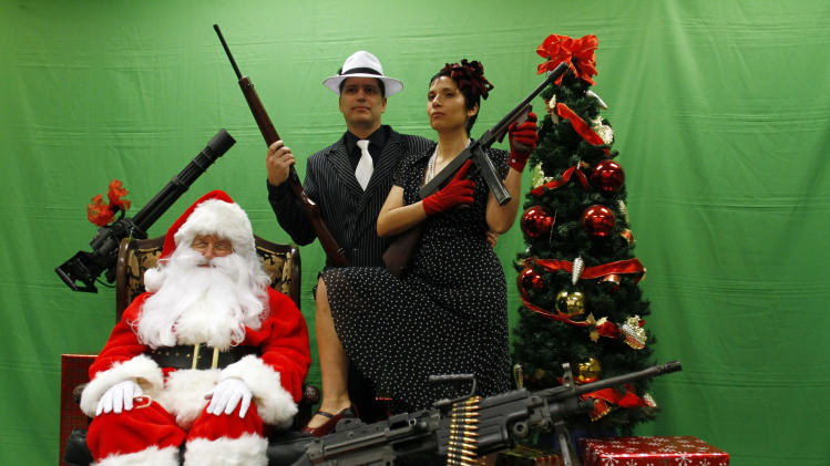 Engle and Engle hold weapons as they pose for a photograph with a man dressed as Santa Claus at the Scottsdale Gun Club in Scottsdale