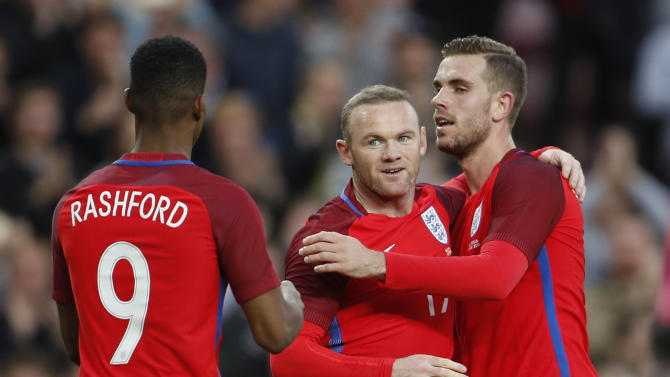Wayne Rooney celebrates with Jordan Henderson (R) and Marcus Rashford (L) after scoring the second goal for England