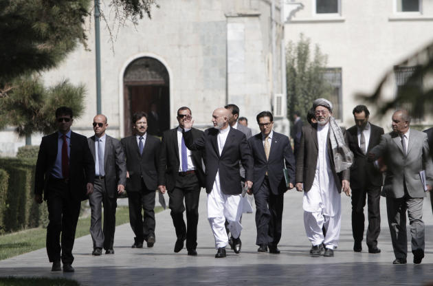 Afghan President Hamid Karzai center, arrives for a press conference at the presidential palace in Kabul, Afghanistan, Monday, Oct. 7, 2013. Karzai says disagreements over security and sovereignty are