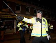 Police charge to disperse demonstrators in Woolich, London on May 22, 2013 after two men wielding knives butchered and beheaded a man believed to be a soldier in a busy London street, before delivering an Islamist tirade to passers-by