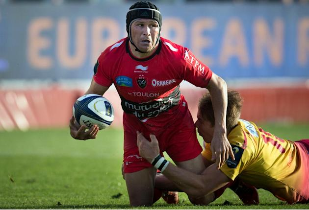 Toulon fly-half Matt Giteau is tackled by a Llanelli Scarlets' player during the European Champions Cup match at the Mayol stadium in Toulon, southeastern France, on October 19, 2014