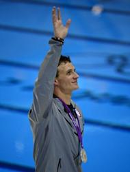 Silver medalist US swimmer Ryan Lochte waves during a lap of honour after the podium ceremony for the men's 200m individual medley swimming event at the London 2012 Olympic Games in London